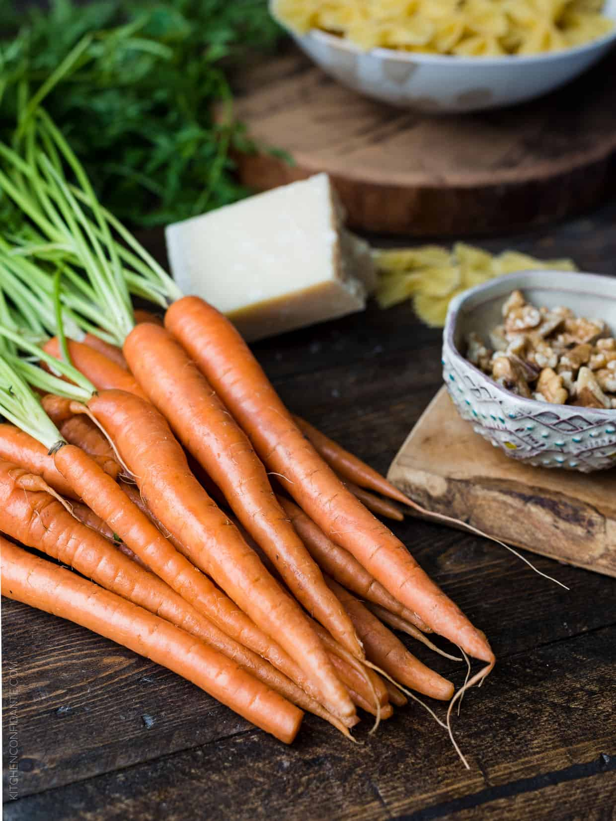 A bunch of raw carrots on a wooden surface surrounded by a block of Parmesan and a bowl of walnuts.