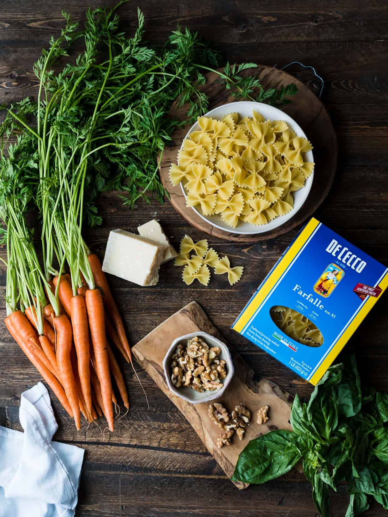 A wooden surface topped with all the ingredients needed to make Farfalle with Roasted Carrot Pesto, Parmesan and Toasted Walnuts.