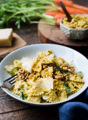 Farfalle with Roasted Carrot Pesto garnished with toasted walnuts and Parmesan cheese on a white plate.