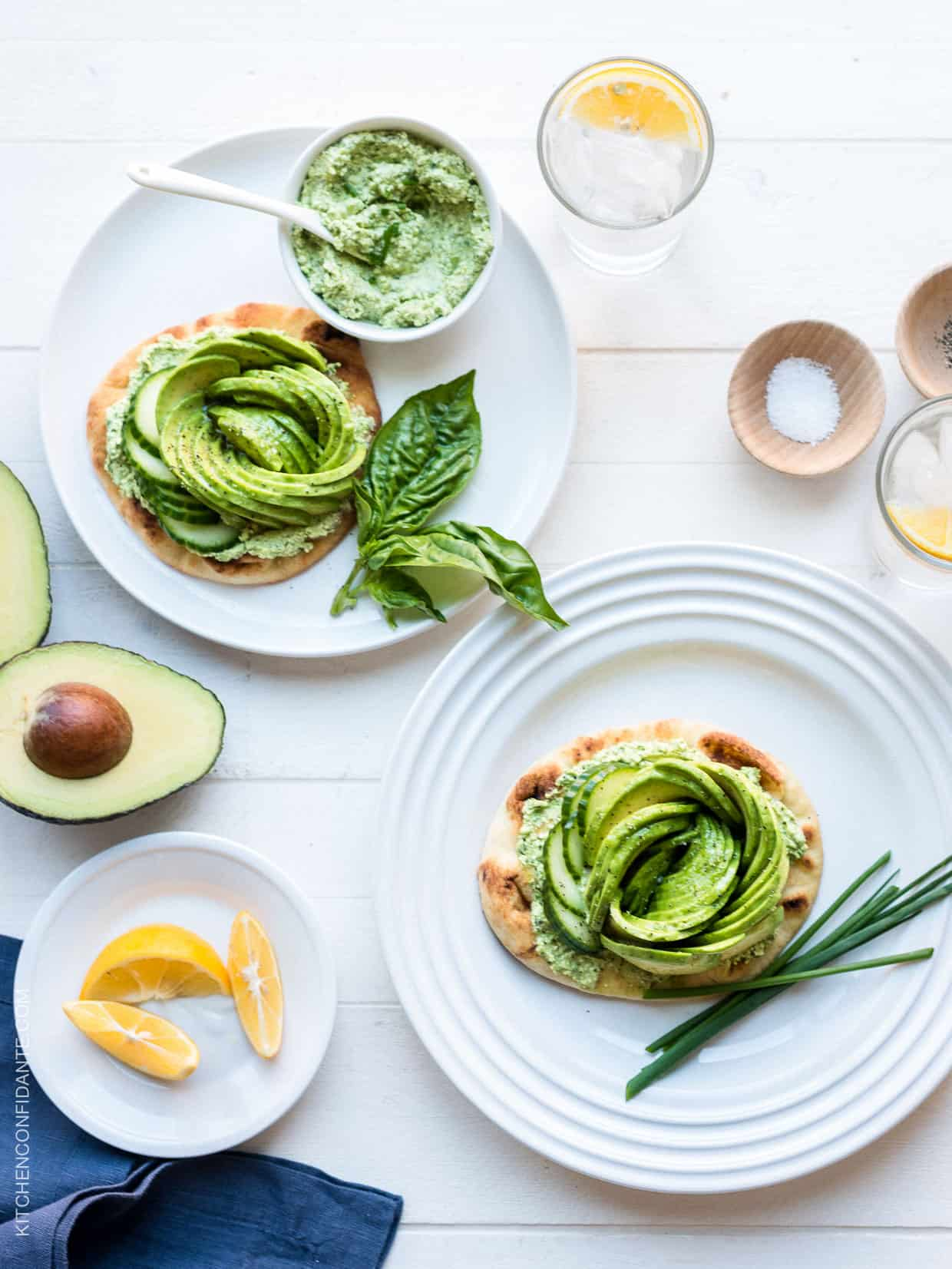 Toasted naan topped with Green Goddess feta spread and an avocado rose served on white plates.