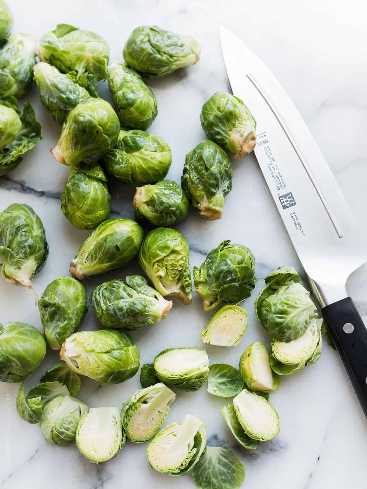 Brussels sprouts split in half on a marble surface alongside a chef's knife.