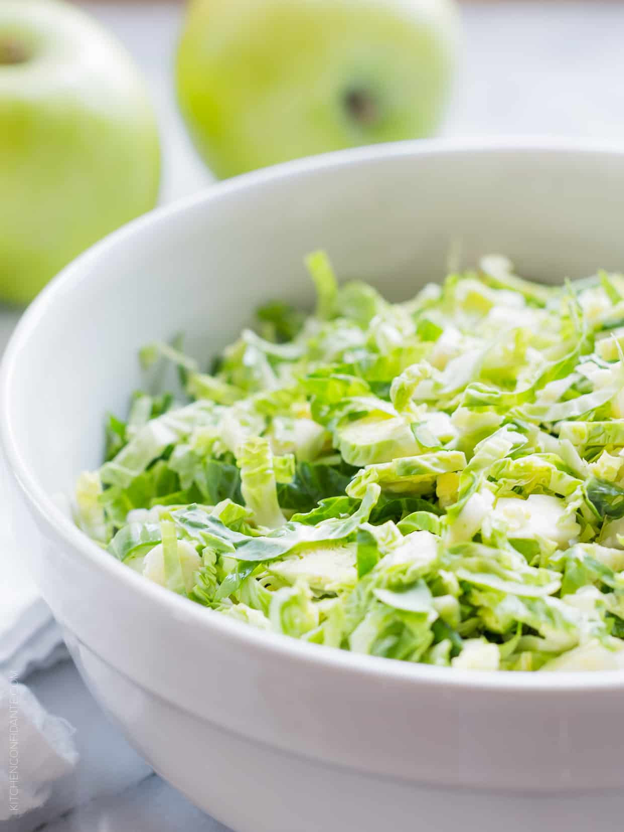 Shredded Brussels sprouts in a white bowl.