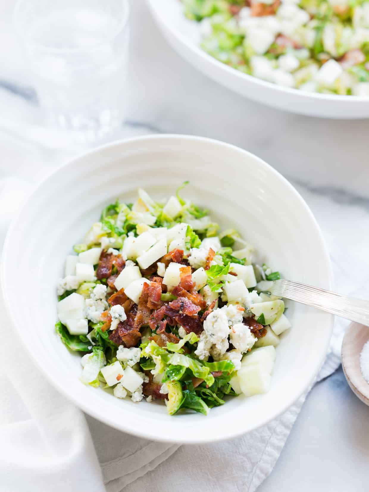 A white bowl filled with Shredded Brussels Sprouts Salad.