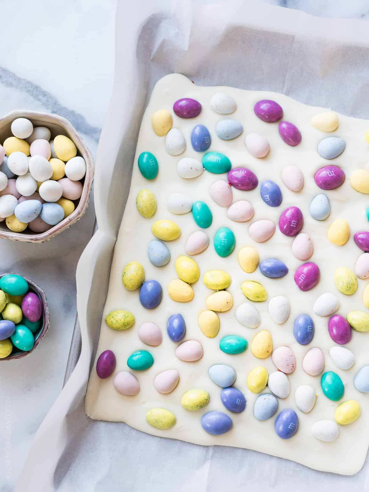 A sheet of White Chocolate Easter Bark on a baking tray surrounded by bowls of candy.