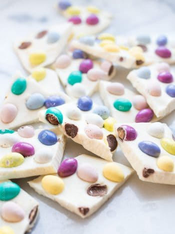 Pieces of colorful homemade White Chocolate Easter Bark on a white surface.