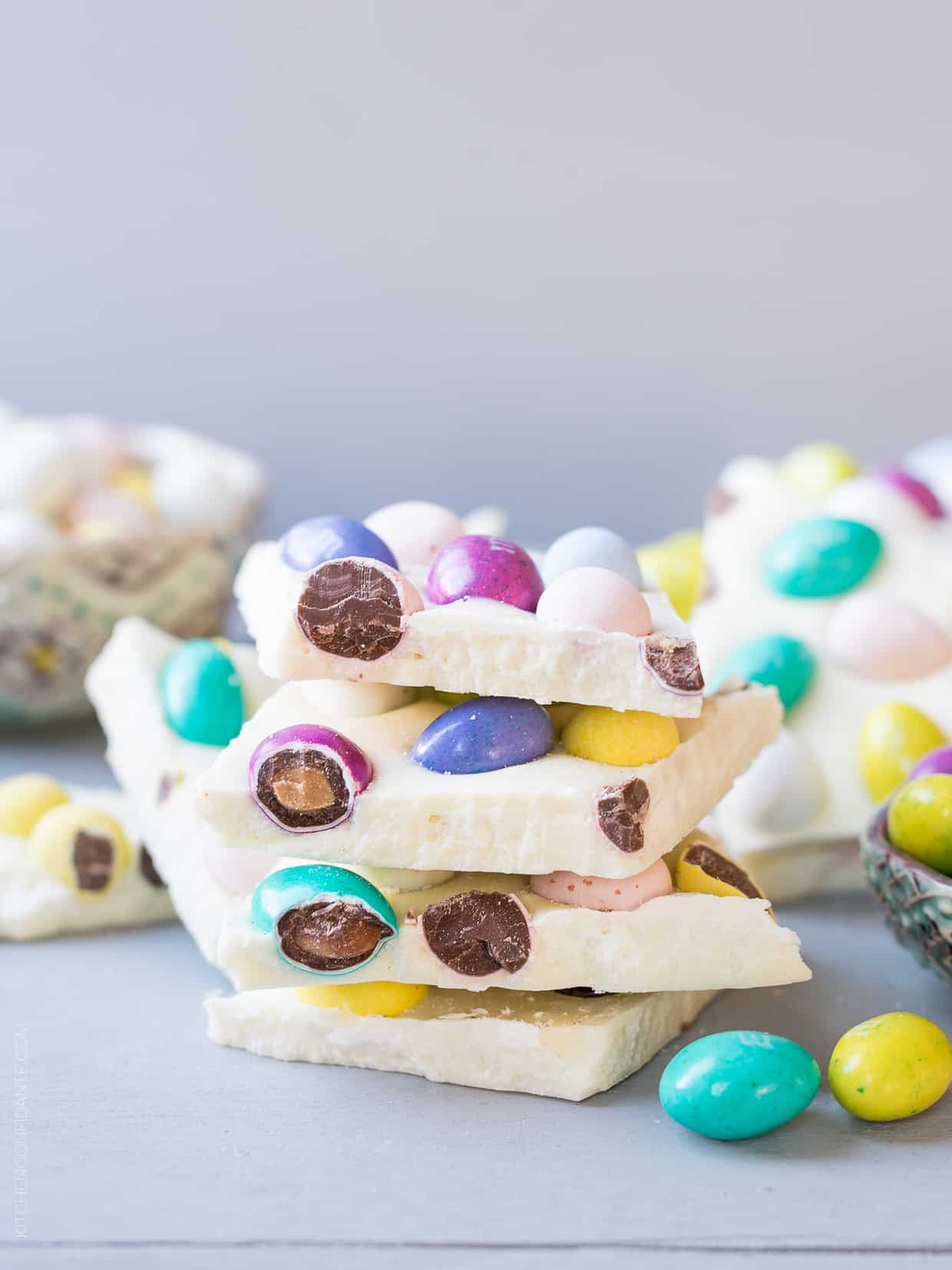 Pieces of colorful White Chocolate Easter Bark stacked on a white surface.