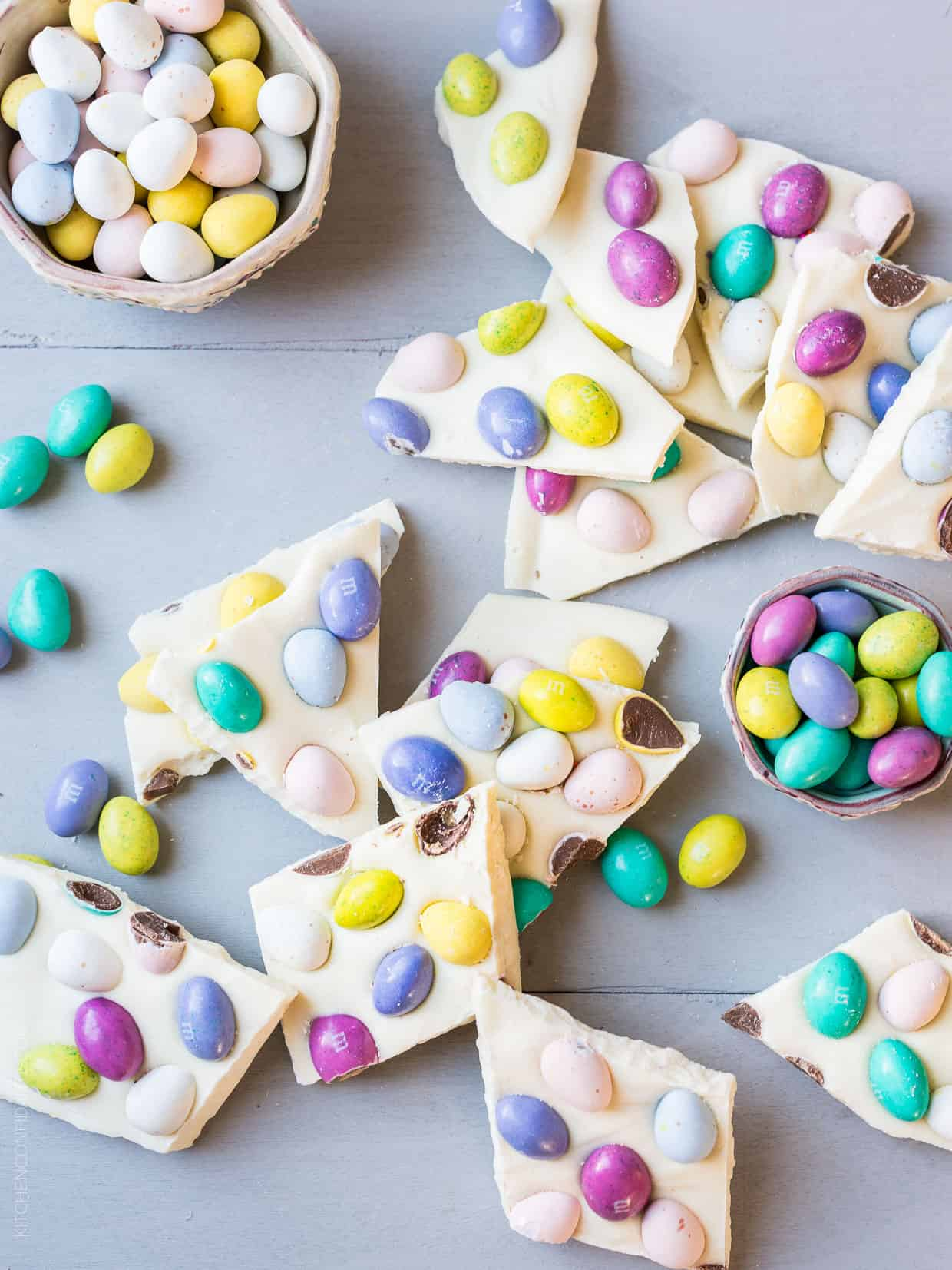 Colorful Easter Bark surrounded by bowls of bright candy eggs.