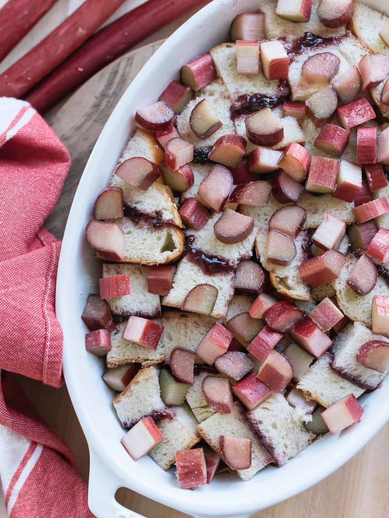 Chopped rhubarb layered with leftover brioche and strawberry jam for Rhubarb Bread Pudding.