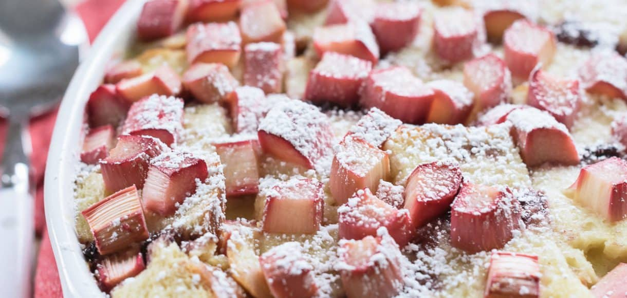 Rhubarb Breading Pudding in a white baking dish on a red and white cloth napkin.