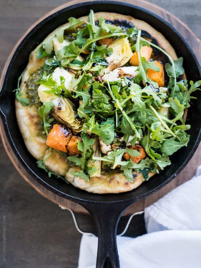 Cast iron skillet filled with Skillet Pesto Flatbread with Goat Cheese, Artichokes and Roasted Butternut Squash.
