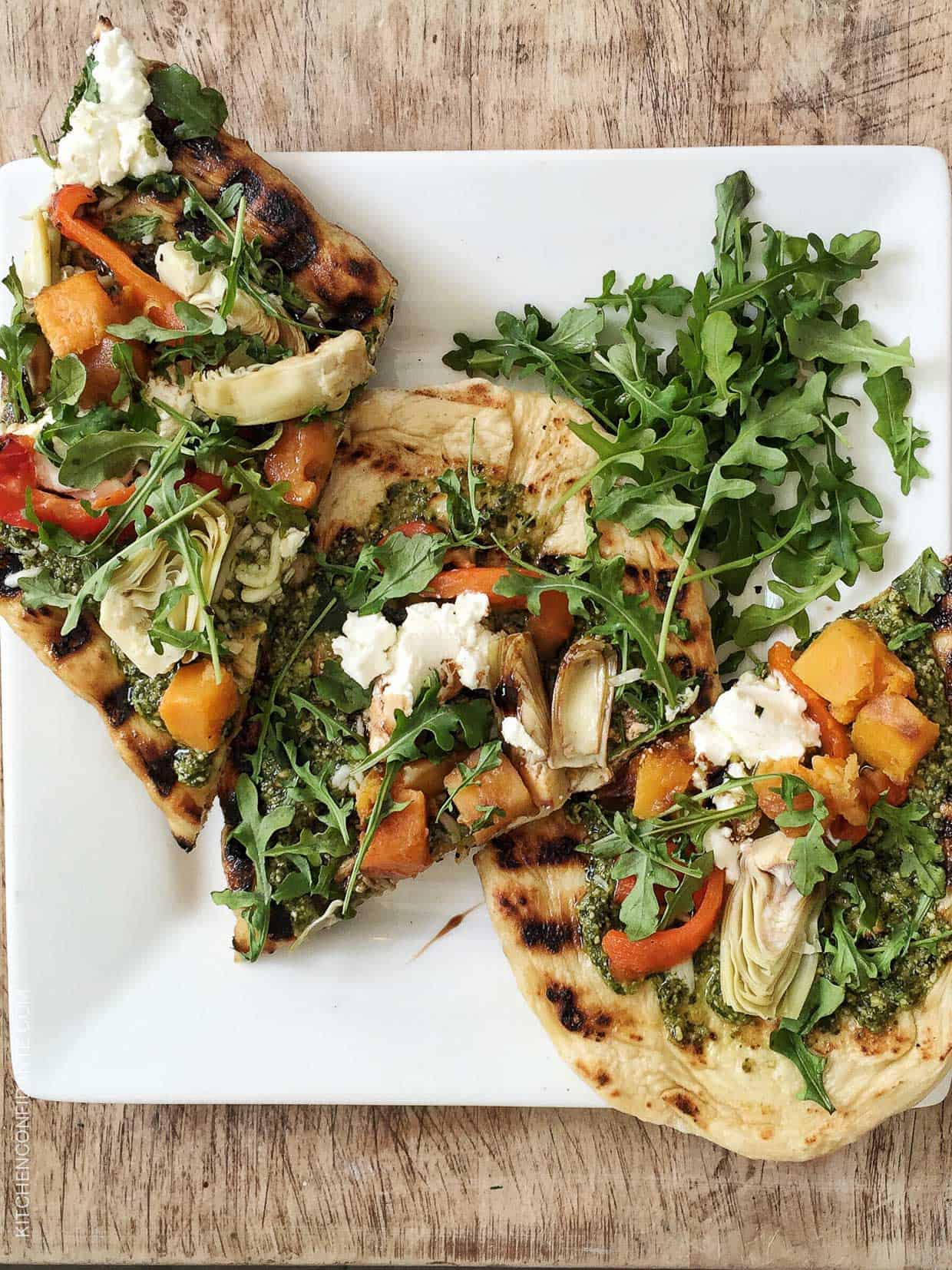 Slices of Skillet Pesto Flatbread with Goat Cheese, Artichokes and Roasted Butternut Squash on a white plate.