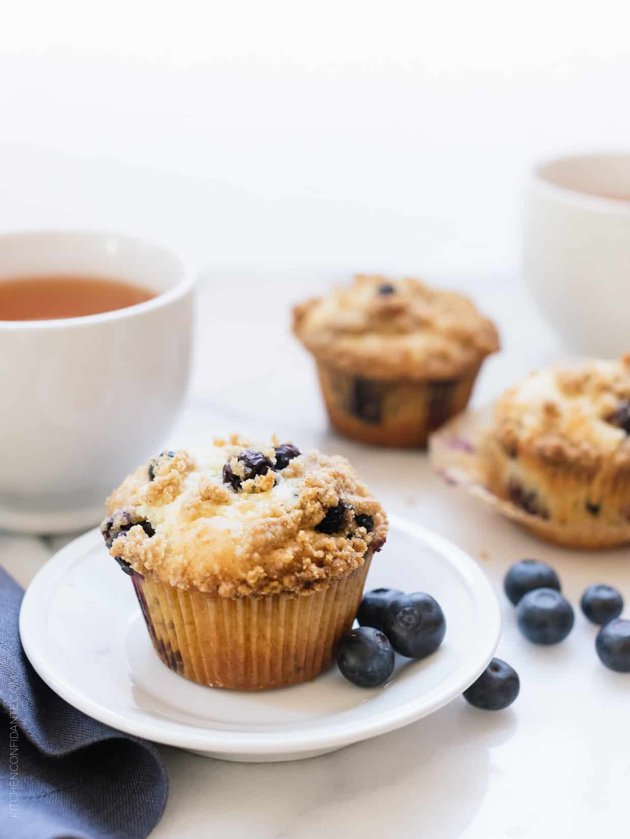 Bakery Style Buttermilk Blueberry Muffins served with a cup of tea in the background and fresh blueberries on the side.