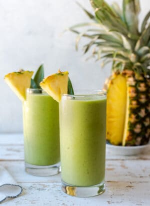 Piña Colada Green Smoothies in glasses garnished with fresh pineapple.