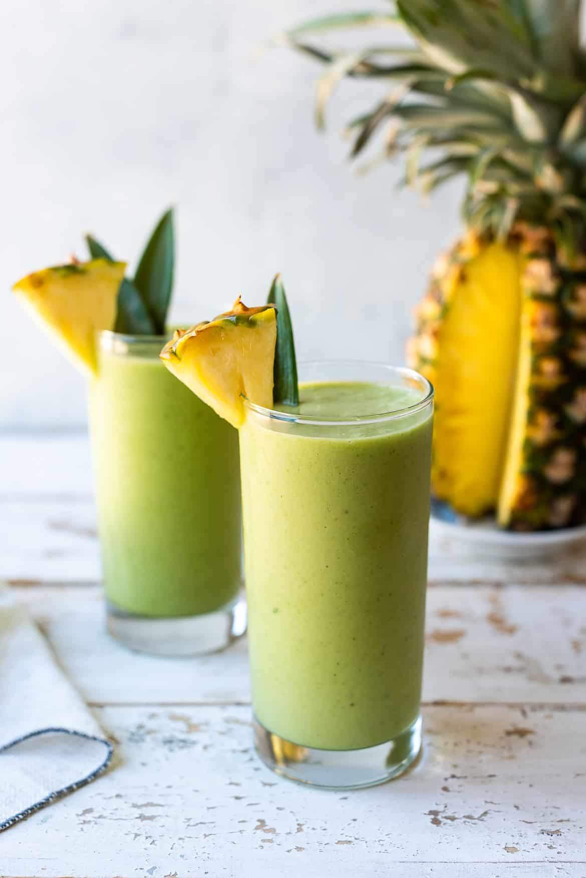 Piña Colada Green Smoothies in glasses with fresh pineapple garnish.