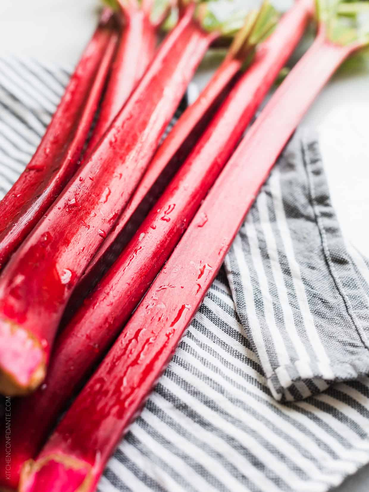 Stalks of freshly washed rhubarb on a blue and white striped towel.