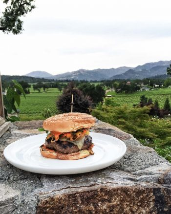 Sweet and Smoky Spanish Beef Burger on a white plate on a rock outdoors.