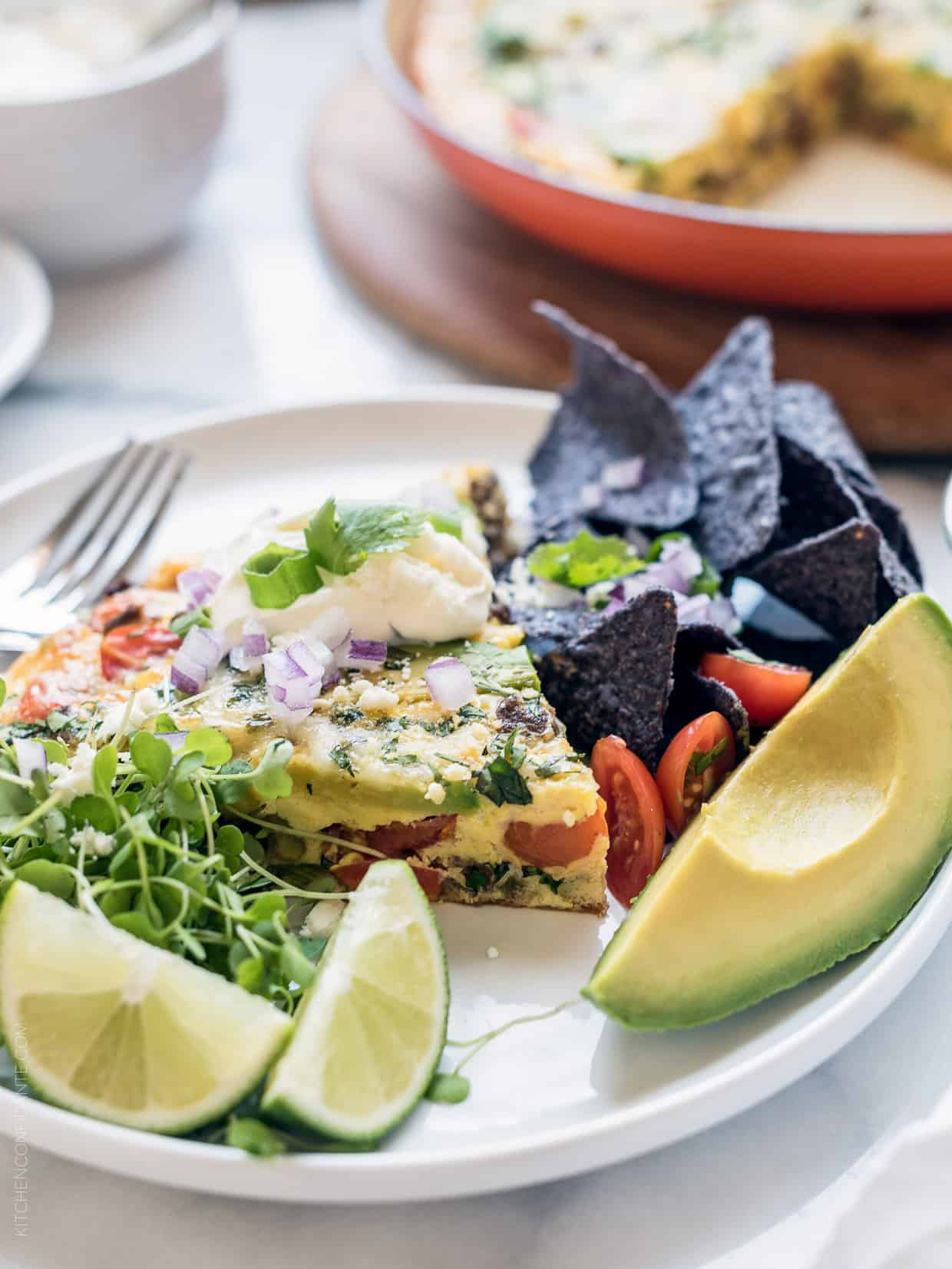Wedge of taco frittata surrounded by a garnish of lime slices, tortilla chips, and avocado.