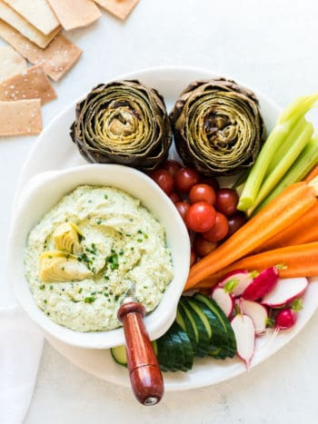A bowl of Artichoke and Avocado Dip surrounded by vegetables including carrots, radishes, and fresh artichokes.