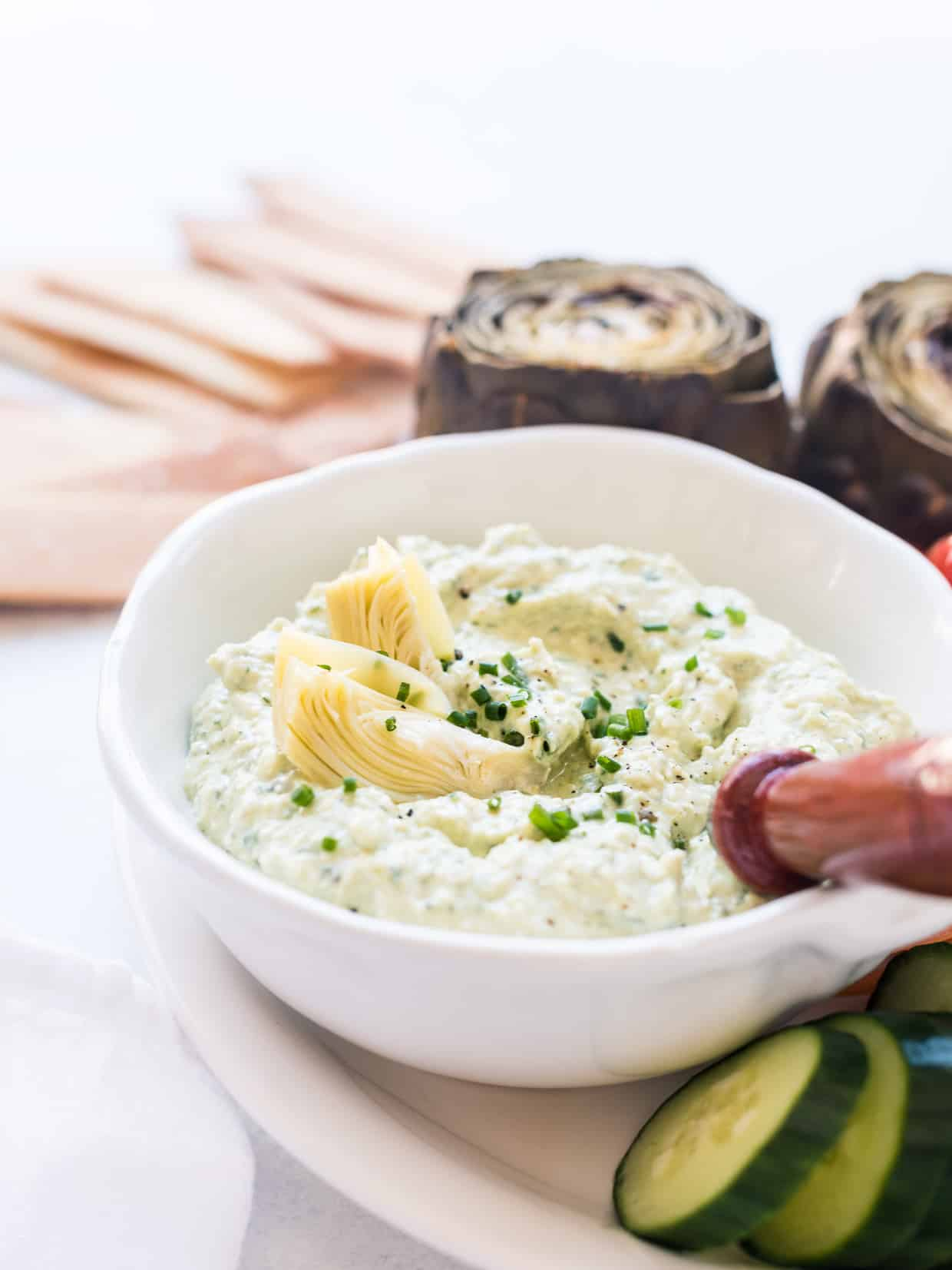 White bowl filled with Avocado and Artichoke Dip.