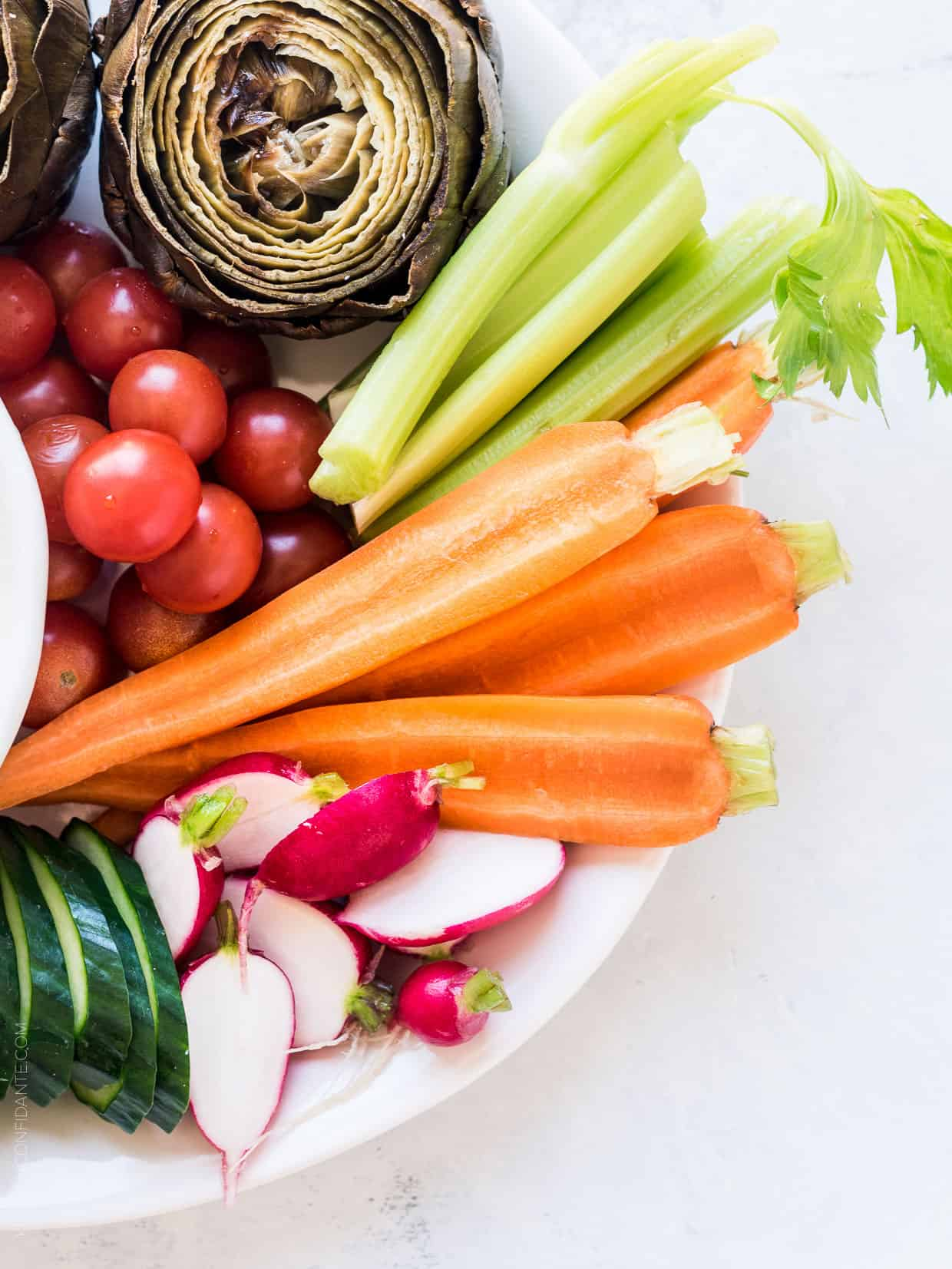 A platter of fresh vegetables including celery, tomatoes, radishes, carrots, and cucumbers.
