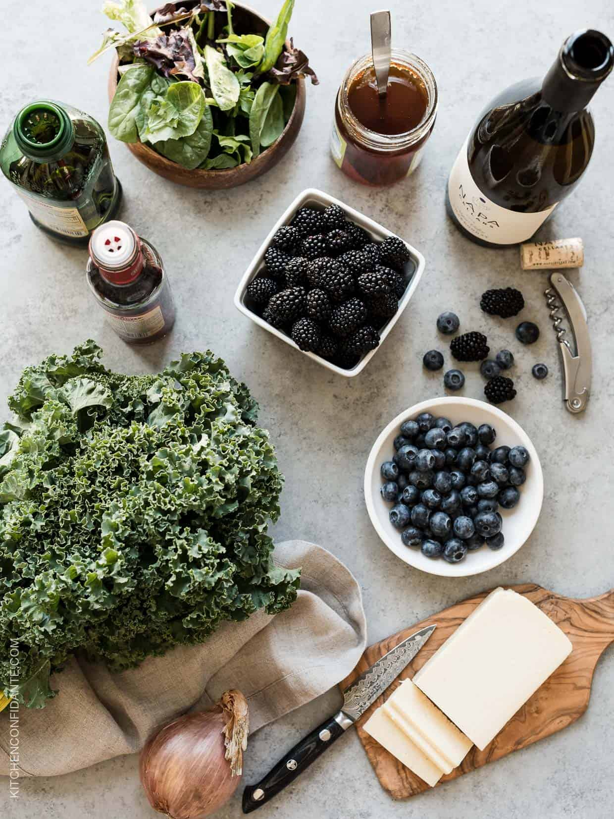 Havarti cheese, fresh blueberries, blackberries and kale on a rustic surface.