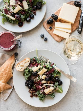 Blackberry and Blueberry Kale Salad with Aged Havarti on a white plate surrounded by sliced cheese and a baguette.