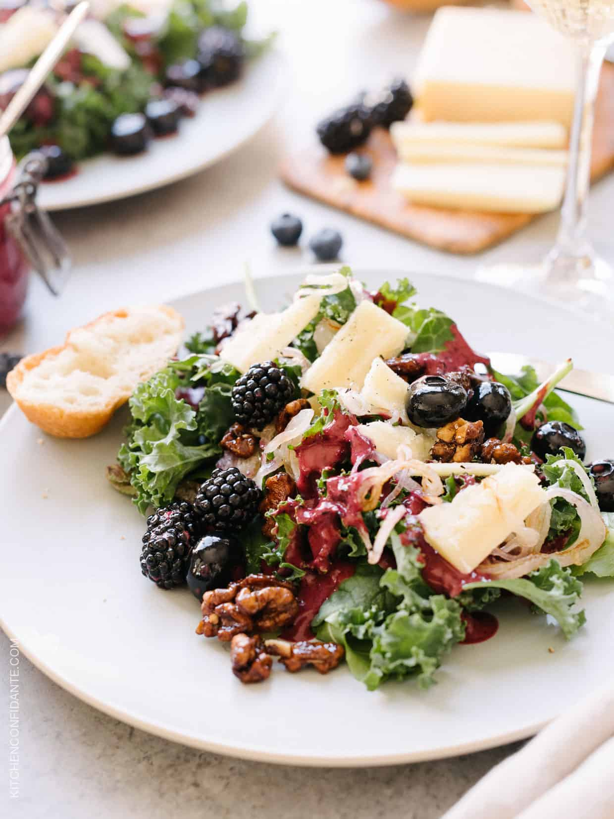 Blackberry and Blueberry Kale Salad with Aged Havarti on a white plate.