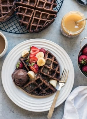 Chocolate Zucchini Belgian Waffles served on a white plate with a scoop of chocolate ice cream, syrup, and fresh fruit.