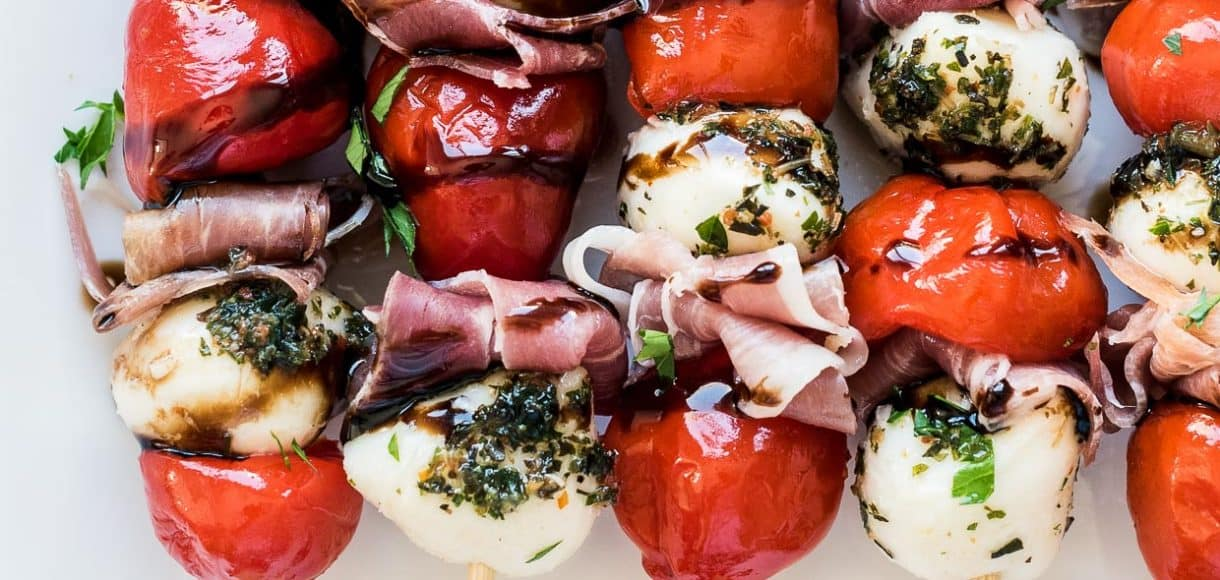 A row of Peppadew Pepper Caprese Skewers with Balsamic Glaze made with fresh mozzarella and prosciutto on a white plate.