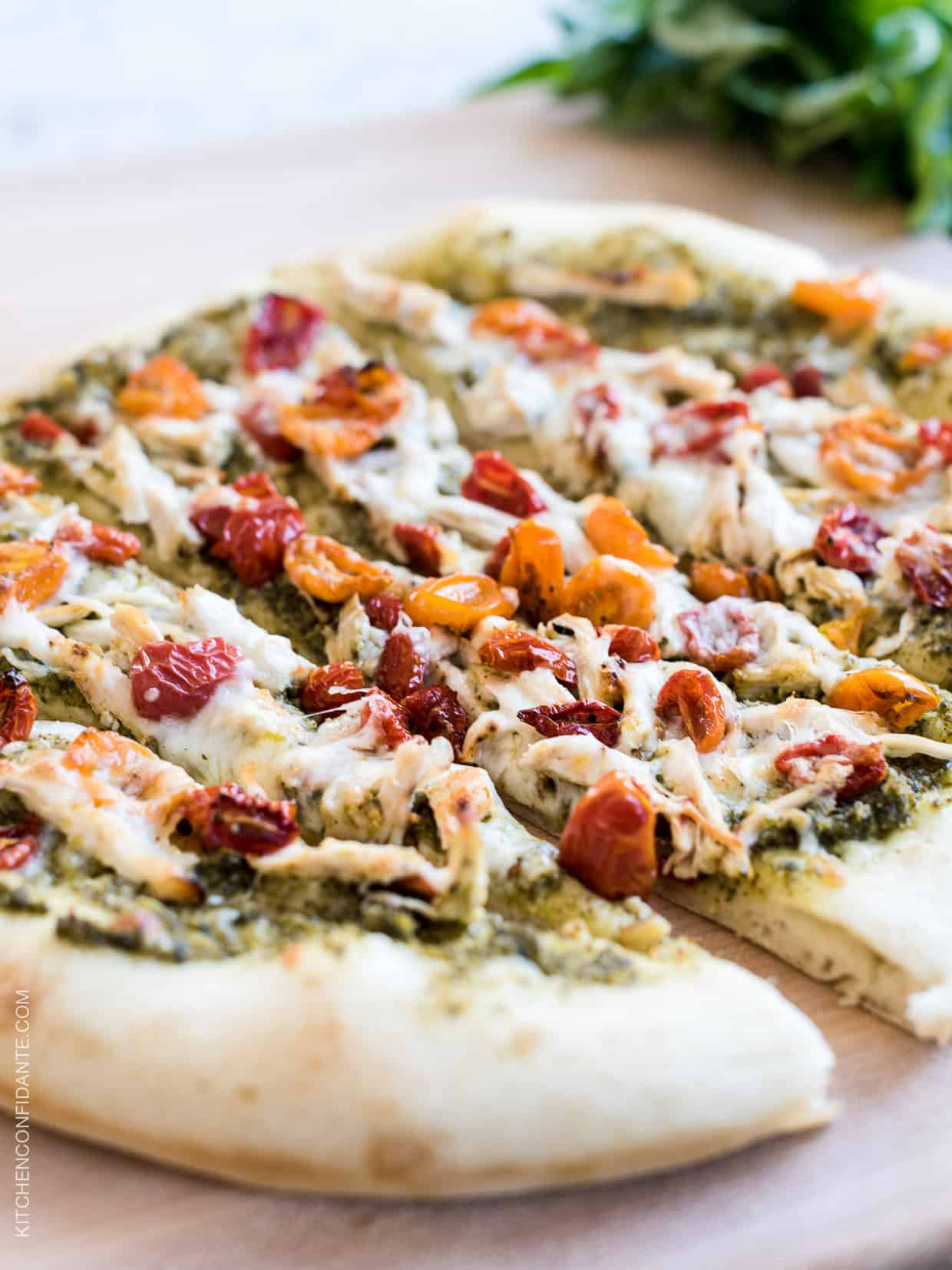 Chicken Pesto Pizza sliced on a wood board.