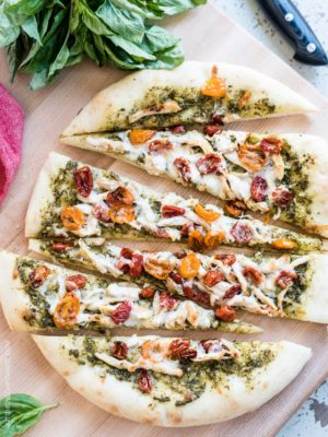 Chicken Pesto Pizza sliced on a cutting board.