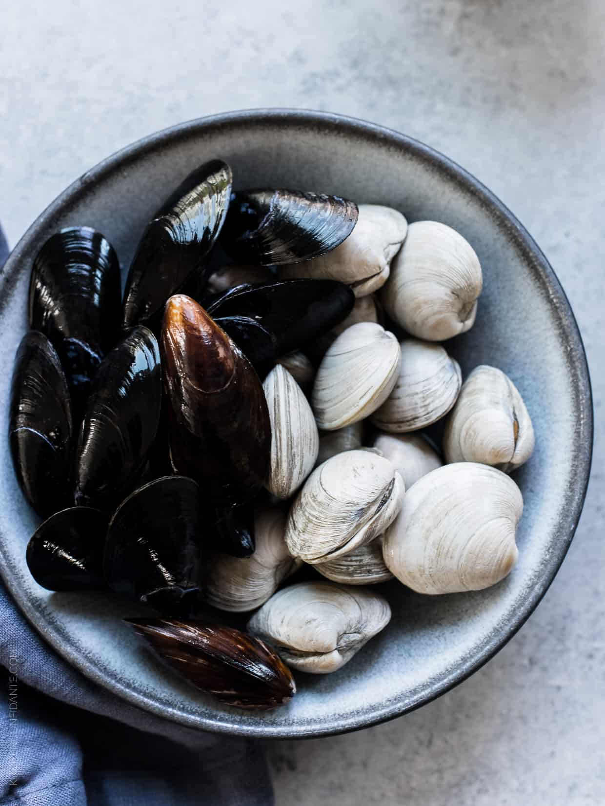 Fresh clams and mussels in a bowl on a rustic surface.