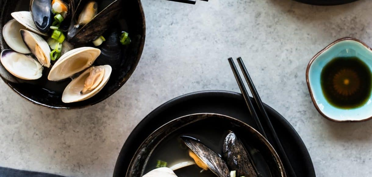 Three black bowls filled with Clam and Mussel Miso Soup and served with chopsticks.