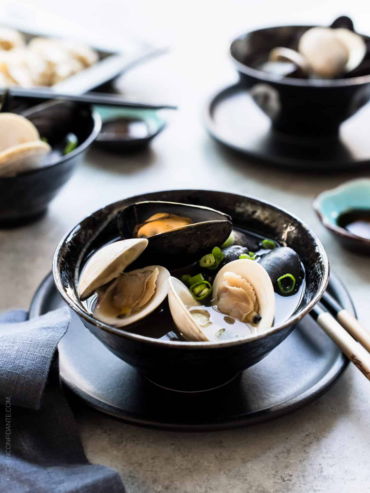 Black bowl filled with Clam and Mussel Miso Soup.
