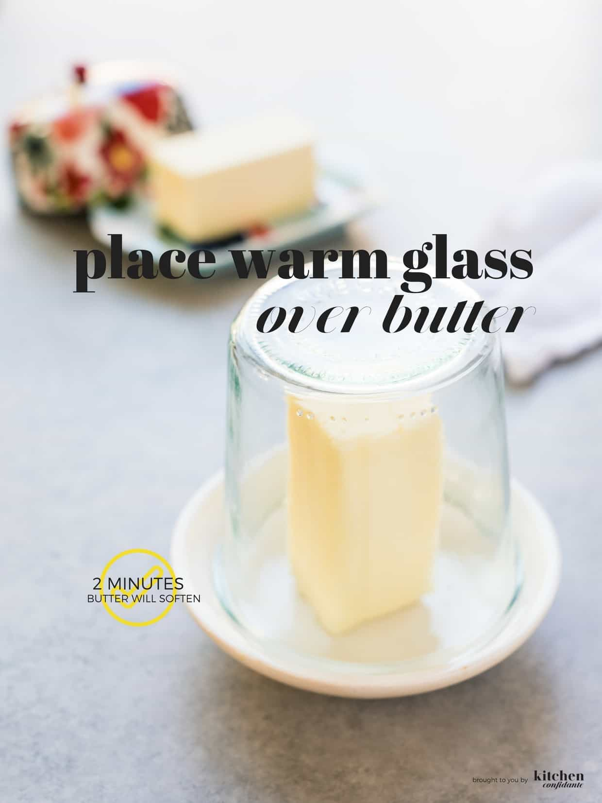 Stick of butter on white plate with a warm glass put over the top to soften it quickly.