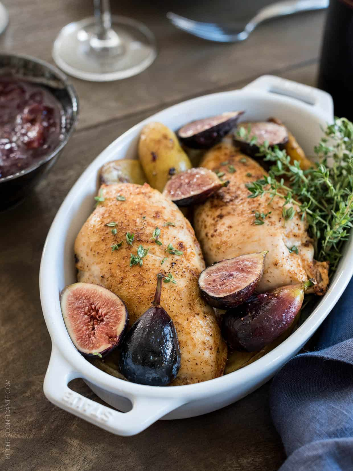 Chicken roasted in a white baking dish with fig chutney.