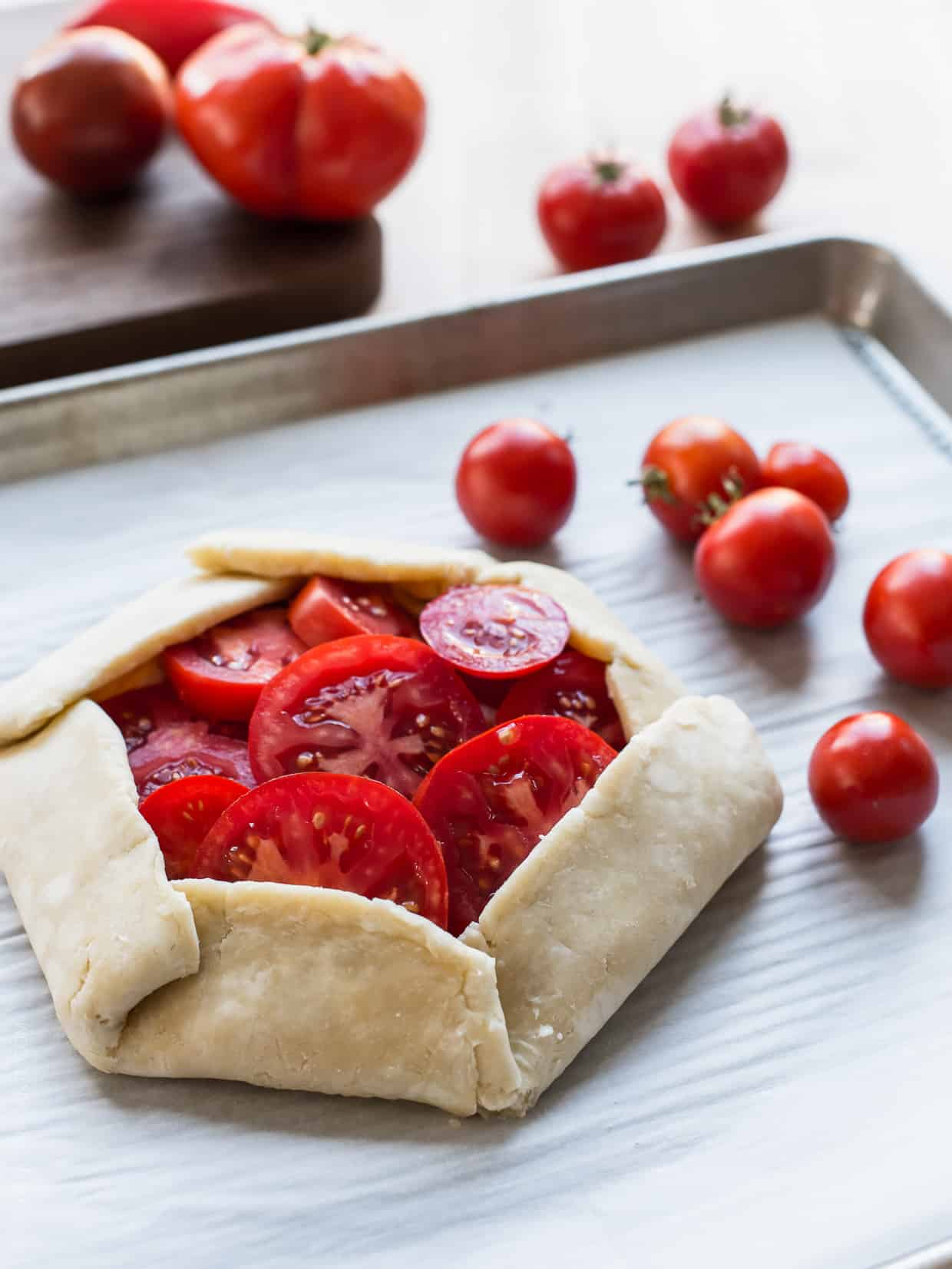 A flaky crust folded around slices of heirloom tomatoes on a baking sheet ready for the oven.