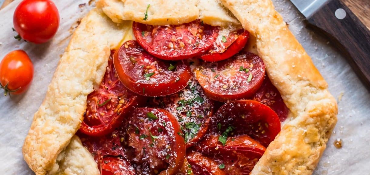 Tomato Ricotta Galette - this rustic pie recipe marries the flavors of pizza with a flakey crust and juicy heirloom tomatoes.