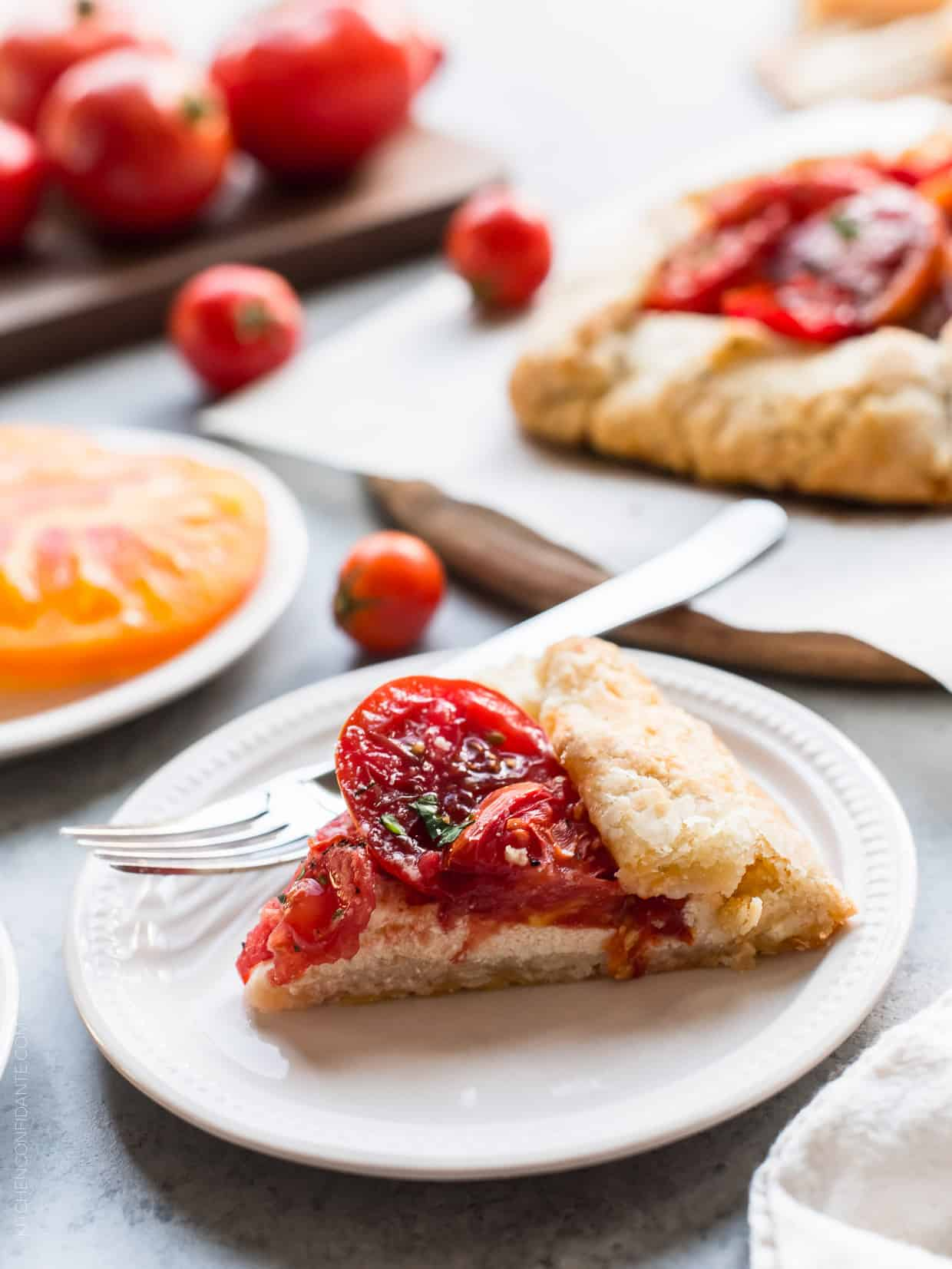 A slice of Tomato Ricotta Galette on a white place with a fork.