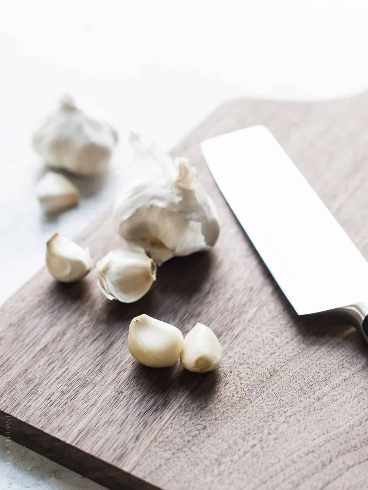 Fresh garlic cloves on a wooden cutting board with a chef's knife.