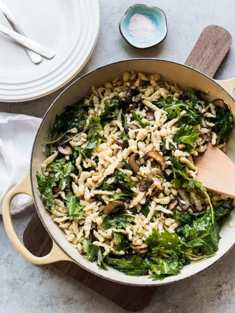 Deep sauté pan filled with homemade Spaetzle with Garlic Butter Mushrooms and Baby Kale.