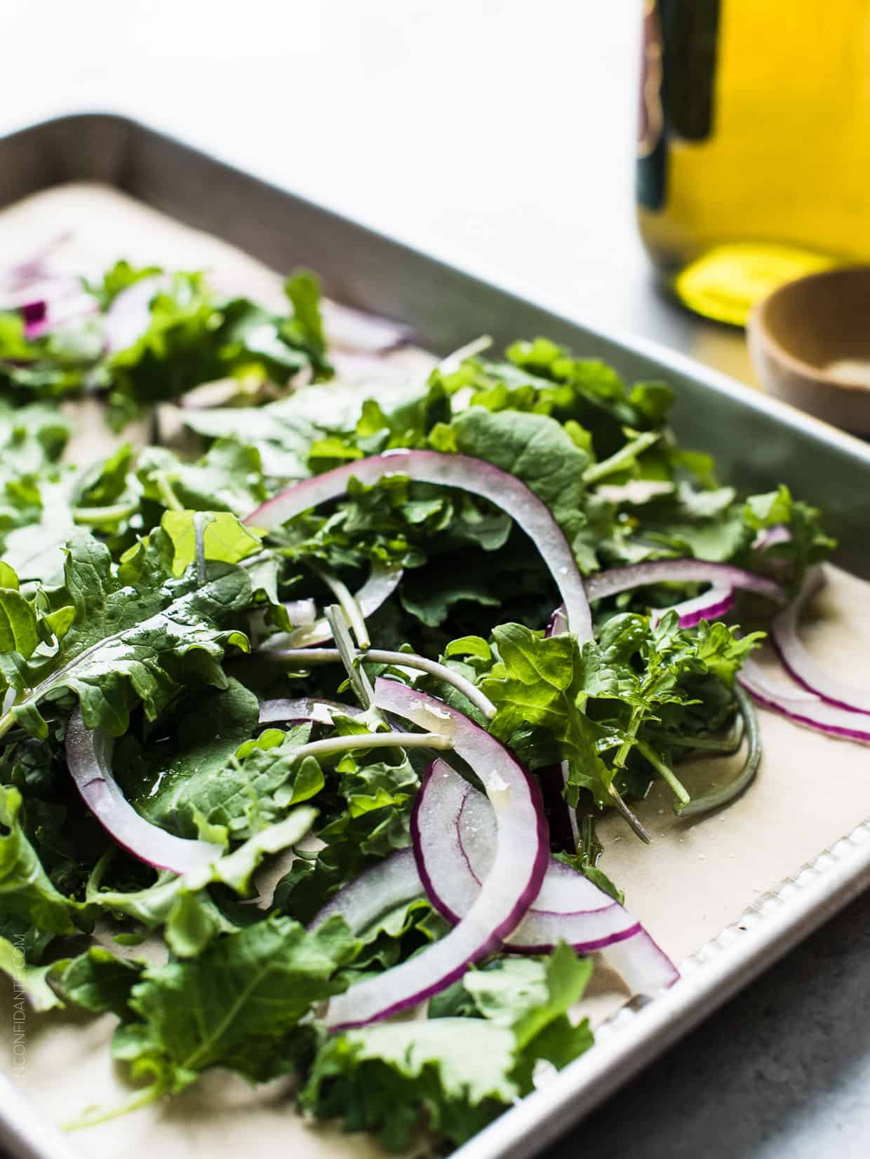 Baby kale and sliced red onion on a baking sheet.