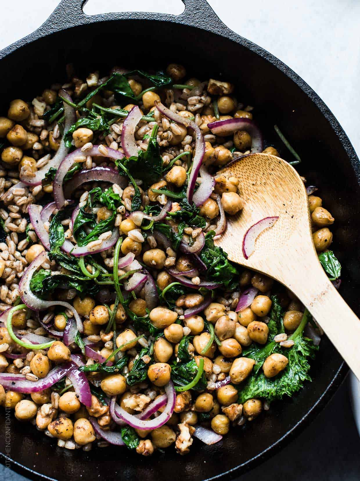 Baby kale, chickpeas, and red onion sautéing in a cast iron skillet.