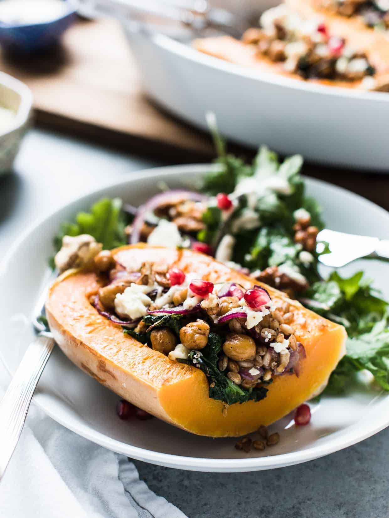 Quartered Stuffed Butternut Squash prepared with chickpeas, farro, kale, walnuts, and more.