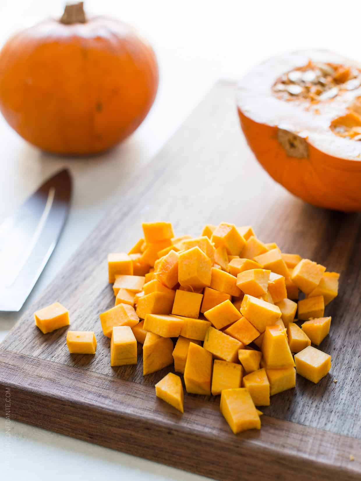 Diced pumpkin chunks on a wooden cutting board ready to be used in Turkey Pumpkin Pot Pie.