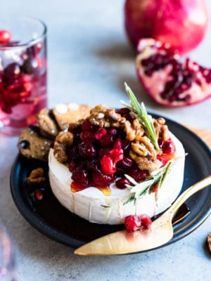 Cranberry Pomegranate Baked Brie served on a black plate with segments of fresh pomegranate in the background.