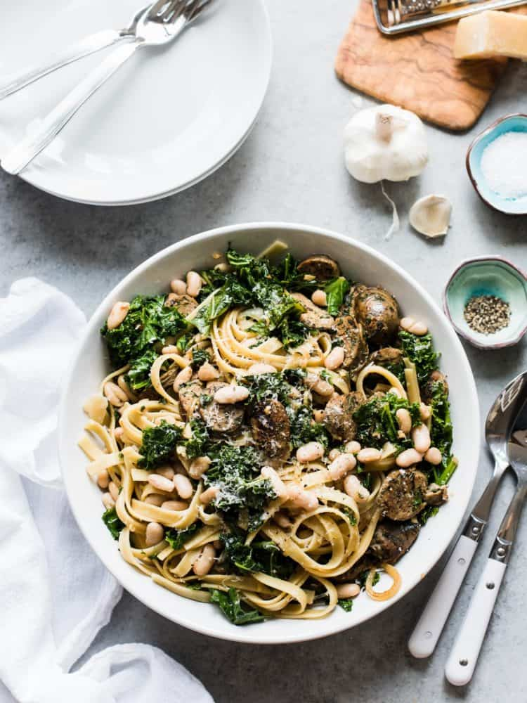Fettuccine with Chicken Sausage, Kale and Cannellini Beans piled high in a white bowl with serving utensils alongside.