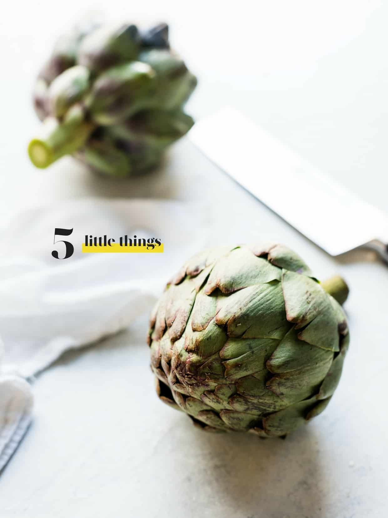 Two artichokes and a knife on a cutting board.
