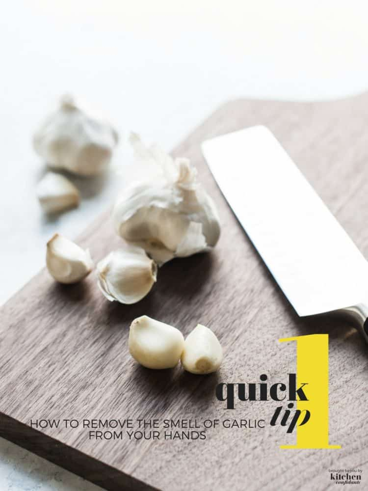 Garlic cloves and a knife on a wooden cutting board.
