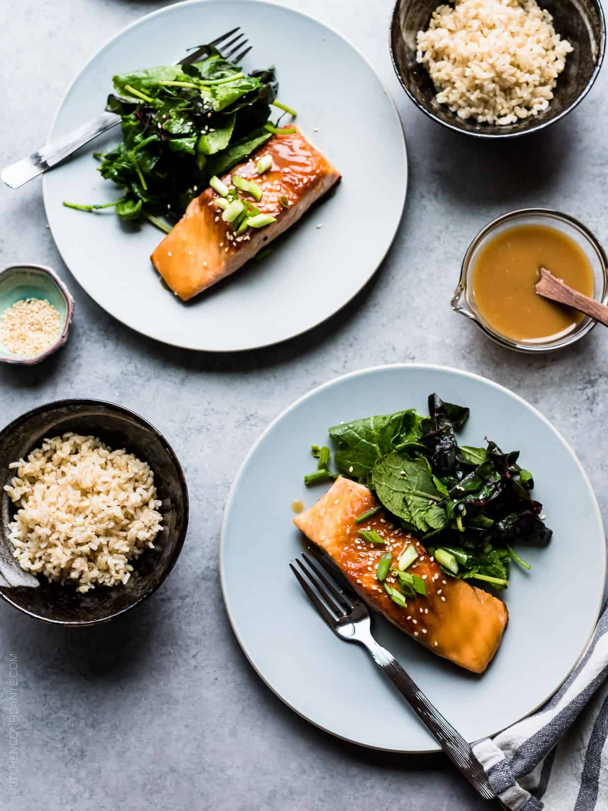 Two white plates filled with Miso Maple Glazed Salmon and wilted green salads served alongside bowls of rice.